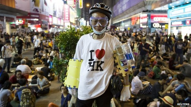 A pro-democracy protester wearing a helmet, goggles and foam pads poses for a picture on a blocked road at the Mong Kok shopping district in Hong Kong, 19 October 2014