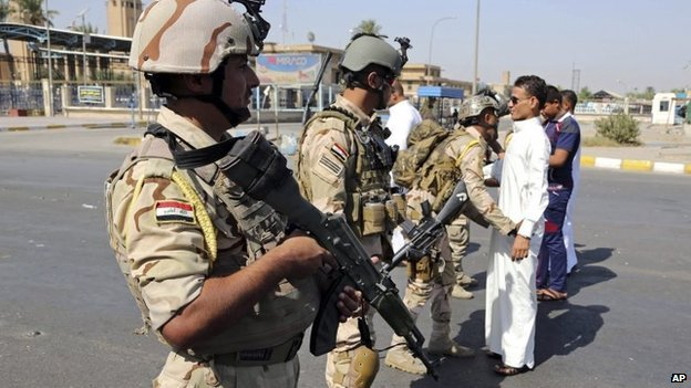 Iraqi Army soldiers search youths amid tight security during Eid al-Adha celebrations in Baghdad, October 6