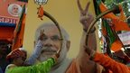 Indian musicians blow trumpets near a hoarding with a portrait of Indian Prime Minister and Bharatiya Janata Party (BJP) leader Narendra Modi during celebrations outside the BJP party office following state elections in Mumbai on October 19, 2014.