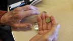 A pensioner holding coins