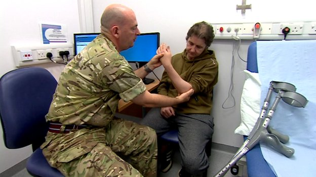 Army surgeon treating a patient