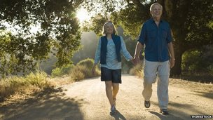 elderly couple walk down path