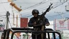 A member of the Mexican Federal Police stands guard in a street of Teloloapan on 19 October, 2014.