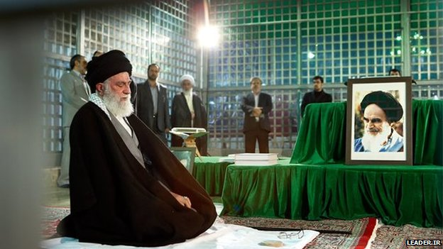 Ayatollah Khamenei (left) next to portrait of Ayatollah Khomeini