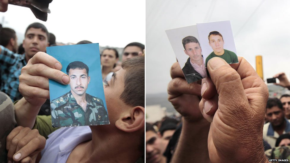 Syrians hold up pictures of missing relatives