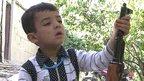 Afghan boy playing with gun