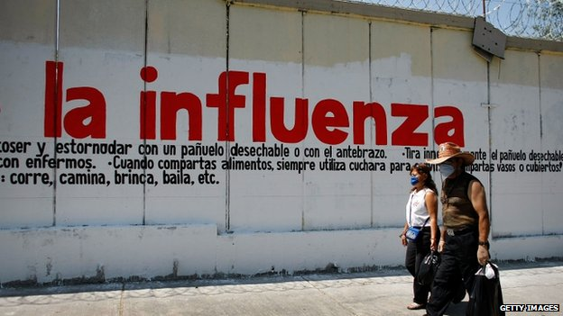 People walk past sign warning of influenza on 1  May 2009 in Mexico City