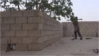 Islamic State fighter firing an RPG from behind a wall