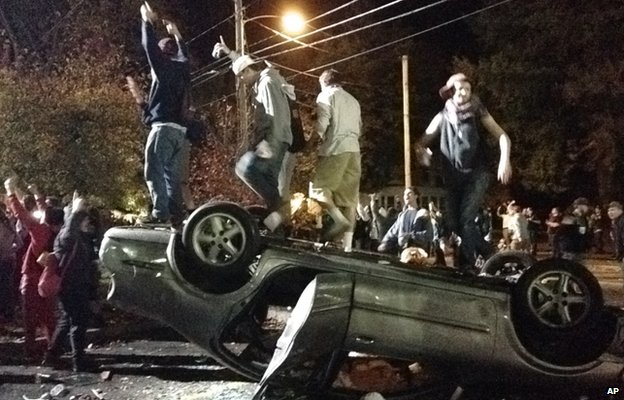 Students on a upturned car in Keene, New Hampshire
