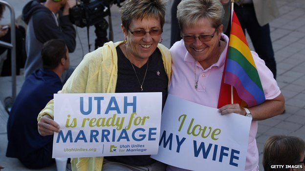 Two women hold signs promoting gay marriage rights outside a Utah courthouse.