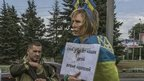"""Irina, tied to a lamppost and draped in a Ukrainian flag, and a sign that reads (in Russian) """"Ukrainian agent and baby-killer"""" next to a soldier"""