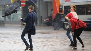 A man holding an umbrella which has been blown inside out by the wind