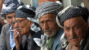 Elderly Iraqi Kurdish men in traditional Kurdish garb sit in the bazaar of Suleimaniyeh, the Patriotic Union of Kurdistan (PUK)-controlled city, some 340km northeast of Baghdad, 17 October 2002