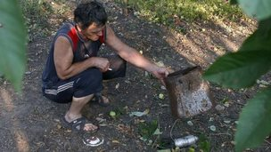 A man shows a dud cluster bomblet in Donetsk, Ukraine, 25 August