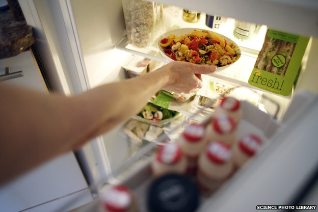 Arm of person putting pasta dish in fridge