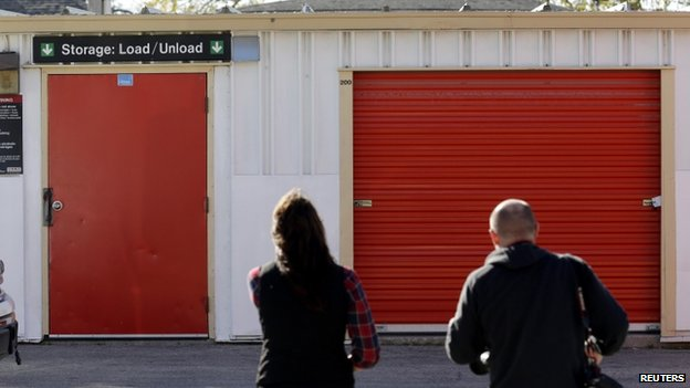 People stand outside a storage facility in Winnipeg, Manitoba, on 21 October 2014