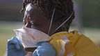 A woman puts on a surgical mask during hospital Ebola training in Alabama.
