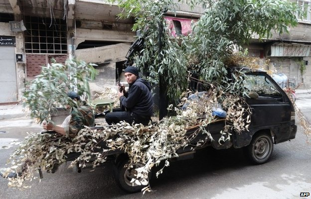 Syrian rebels in a camouflaged lorry in the rebel-controlled area of al-Hajar al-Aswad, south of Damascus (19 October 2014)