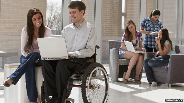 A man in a wheelchair looking at his laptop with a woman sitting next to him.