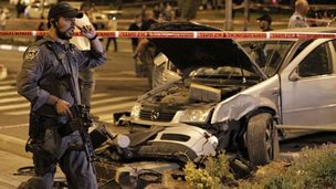 Israeli policeman stands near the car that hit pedestrians at Ammunition Hill light rail station in Jerusalem (22 October 2014)