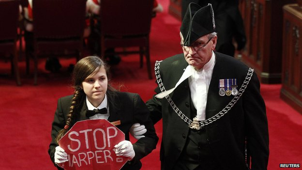 "Senate page Brigette DePape, holding a sign reading ""Stop Harper"" is led from the room by Sergeant-at-Arms Kevin Vickers (R) in the Senate chamber on Parliament Hill in Ottawa in this file photo from June 3, 2011."