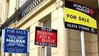 Estate agent signs outside properties in Brunswick Square, Brighton