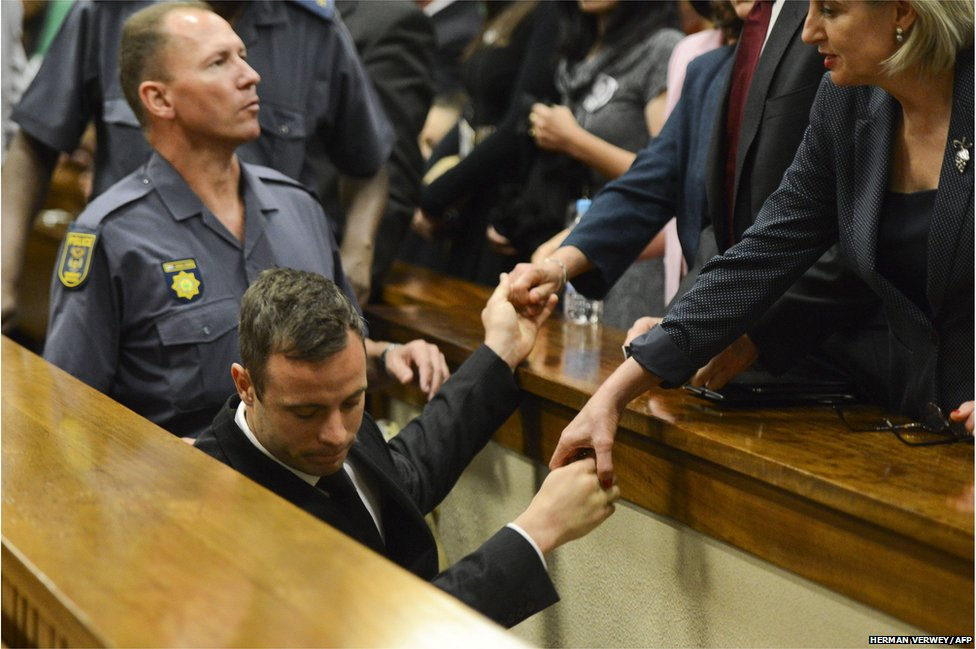 Oscar Pistorius holds the hands of family members as he is taken down to the holding cells