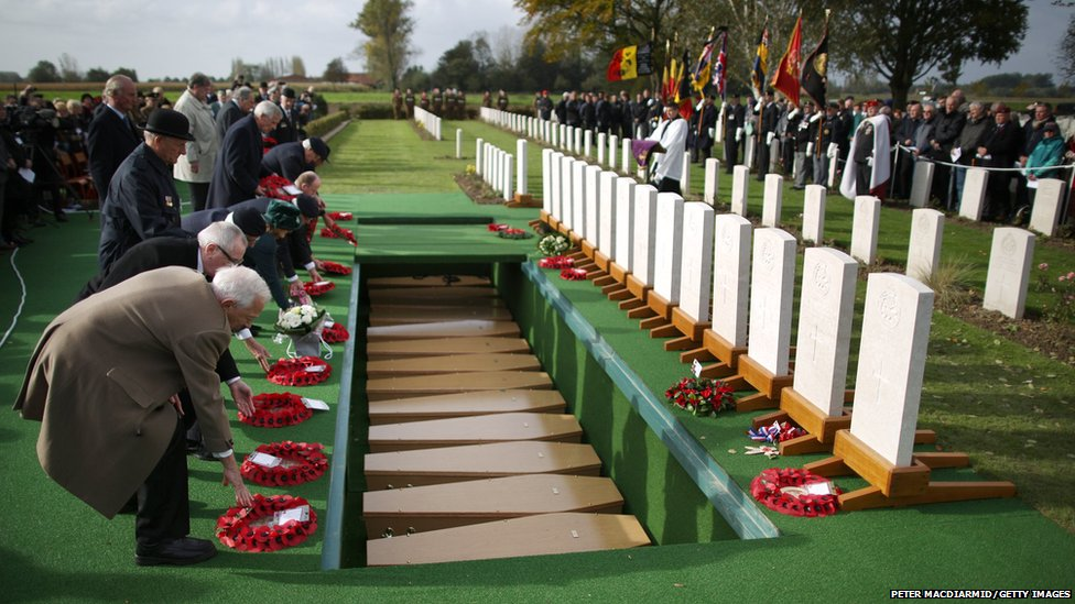 Veterans lay wreaths next to coffins containing the remains of 15 British World War One soldiers