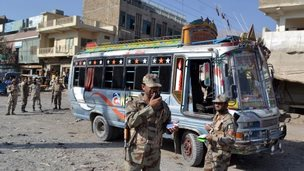 Pakistani security officials inspect the site of an incident were unknown assailants opened fire on a bus in Hazara Ganji area of Quetta, Pakistan, 23 October 2014