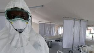 A health worker in Guinea poses inside inside a tent in the Ebola treatment unit - October 2014