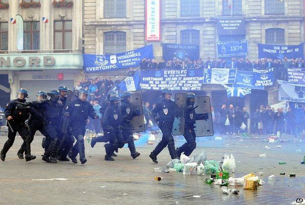 French riot police officers run after soccer fans during clashes which broke out in the main square of Lille,