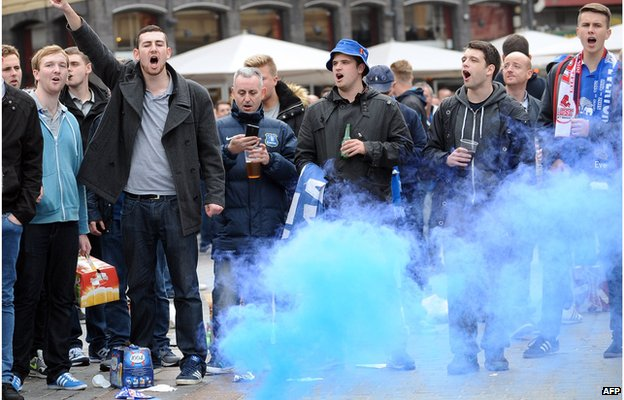 Everton's supporters sing as they stand next to a burning blue flare on the Grand Place