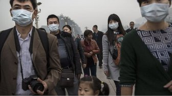 Chinese adults wear masks on a smoggy day near Tiananmen Square on 19 October, 2014 in Beijing, China