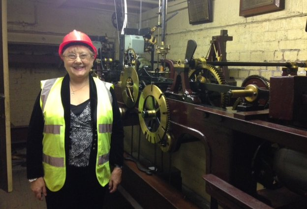 Faye Cunningham in front of clock mechanism