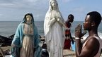A man praying before a statue of the Virgin Mary amid debris on a beach in Port Bouet, Ivory Coast - Thursday 23 October 2014