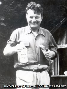 Malcolm Lowry holding a bottle of gin outside his cabin in Dollarton, Vancouver, 1940s