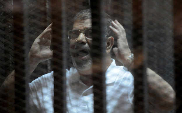 Egypt's ousted President Mohammed Morsi inside the defendant's cage at his trial