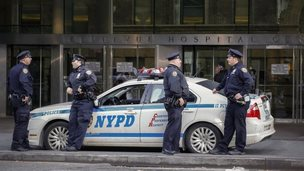 Police officers stand guard in front Bellevue Hospital where Dr Craig Spencer who was diagnosed with the Ebola disease remains in quarantine, on 25 October 2014 in New York City.