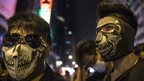 Masked protesters stand at the barriers dividing the police from the crowds in Mongkok October 25, 2014 in Hong Kong