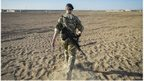 A British officer walks on deserted ground inside Camp Bastion