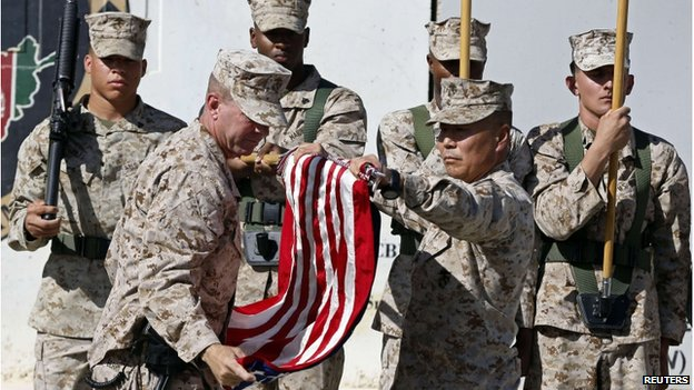 US military personnel taking down a US flag