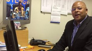 The BBC's Johannesburg correspondent Milton Nkosi behind his desk in Johannesburg and answers the questions by social media users