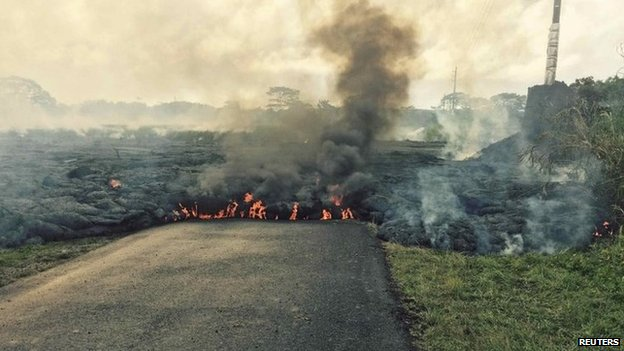 The lava flow from the Kilauea Volcano is seen crossing Apa'a Street/Cemetery Road in this U.S. Geological Survey (USGS) image taken near the village of Pahoa, Hawaii 25 October 2014