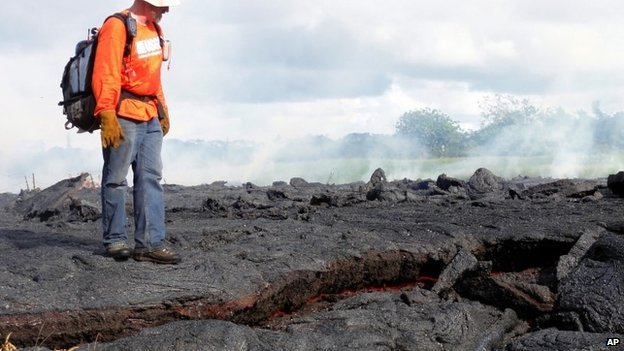 This Oct. 25, 2014 photo provided by the U.S. Geological Survey shows a Hawaii Volcano Observatory geologist standing on a partly cooled section of lava flow near the town of Pahoa on the Big Island of Hawaii.