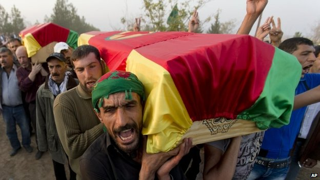 The coffins of Syrian Kurdish Popular Protection Units (YPG) fighters are carried by Kurds in the Turkish town of Suruc (28 October 2014)
