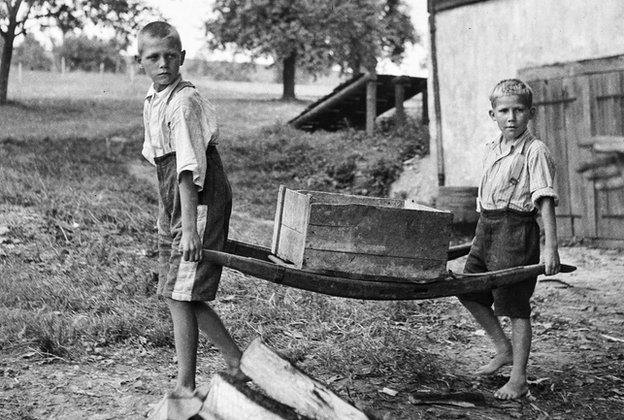 Two boys with no shoes carrying a crate