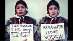 One woman holding a sign saying 'I am Russian I sell drugs' and another holding up a sign saying 'Vodka water'