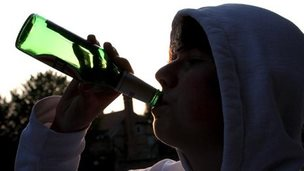 Teenager drinking alcohol from a bottle