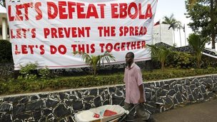 Man walking past Ebola sign