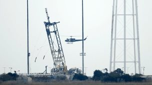 A helicopter does reconnaissance over the launch pad at NASA Wallops Flight Facility in Virginia on 29 October 2014